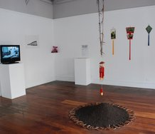 The Chinese Horoscope Show at Enjoy. On floor, Tiffany Singh, Never Follow a Straight Line, 2012, dirt, horse shoes, horse hair, painted bamboo wind chime.  On back wall on the right, Kate Woods, Untitled, 2012, photographs, fringing.