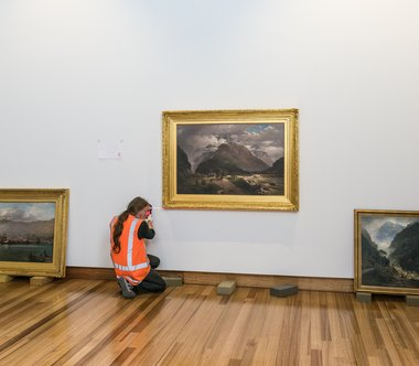 Staff install John Gibb's Clearing up after rain, foot of Otira Gorge, 1887, oil on canvas. Purchased, 1964. Photograph by John Collie, Christchurch Art Gallery, Te Puna o Waiwhetu
