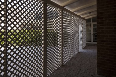 Charlotte Drayton, It must be nice to work outside on a day like today, 2016, pregrown kapuka (griselinia) hedges, crushed shell, trellis, paint (alabastaer White), concret pavers, irrigation system, commissioned by Te Tuhi. Photo: Sam Hartnett