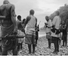 "Photograph on page 4 of The Black Islands. Bohane's note reads '""Warlord"" Harold Keke (centre, praying) and his GLF (Guadalcanal Liberation Front) guerrillas pray on a beach before patrolling, along the Weathercoast, Guadalcanal, Solomon Islands 2013.'"