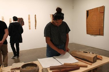 A visitor to Papakura Art Gallery examines the notebook in which Nikau Hindin has recorded her research into aute.
