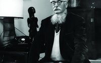 William Empson posing with an unidentified sculpture.