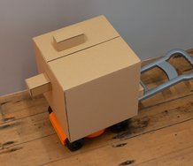 PĀNiA!, Honorary Consulate (Mobile Cardboard Detachment) (2019), cardboard, adhesive, masking tape, plastic toy lawn mower.  49 x 31.5 x 78 cm.  Photo: Arekahānara