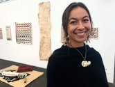 Nikau Hindin poses in front of the works she was installing at Te Uru. Image from the website of Maori TV, May 2019.